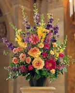 Peach roses,purple larkspur,pretty gerbers,sweet heart roses ec. make this a beautiful mixed arrangementt