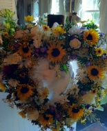 Beautiful Sun Flowers arranged with white roses etc. for a comforting Service